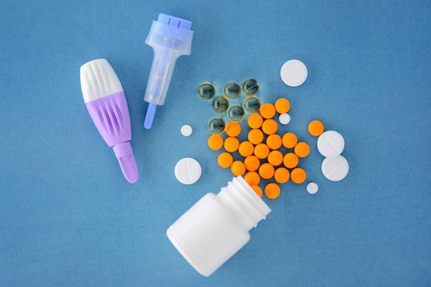 Comprimidos e lancetas adulto e crianças em um fundo azul.