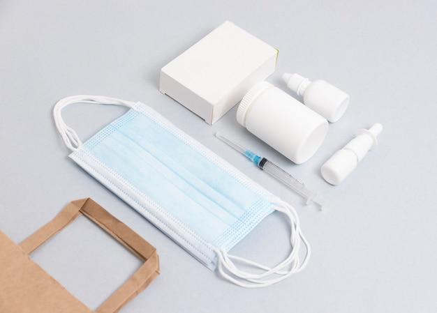 Comprimidos e máscaras médicas encontram-se sobre um fundo azul. conceito de entrega de drogas médicas.