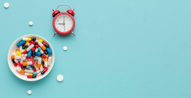 Comprimidos e relógio na mesa com cópia-espaço