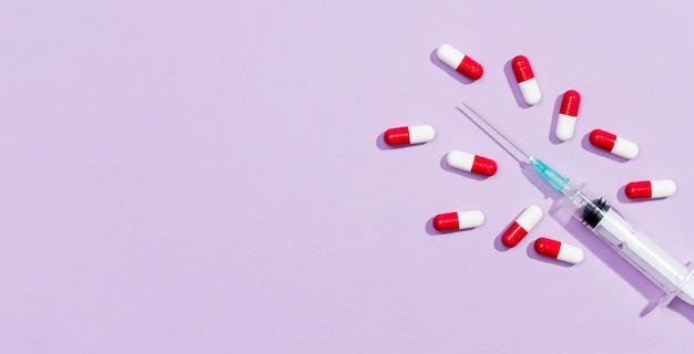 Comprimidos e seringa de cópia-espaço