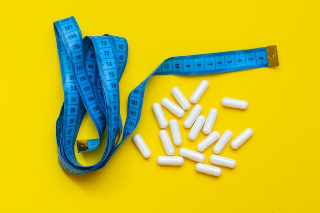 Comprimidos e uma fita métrica em um fundo amarelo, o conceito de perder peso