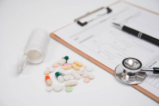 Comprimidos e uma garrafa branca, junto com um estetoscópio e uma ficha médica, estão sobre um branco. usado para saúde ou conceito de indústria de fabricação médica.