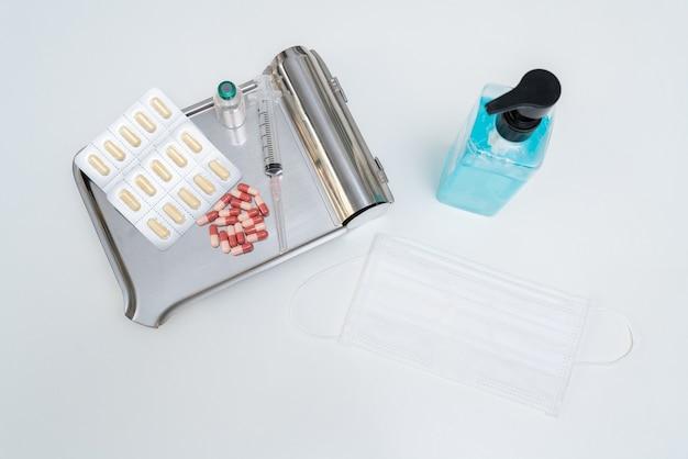 Comprimidos e vacina com seringa, máscara e gel de álcool em uma bandeja no fundo branco