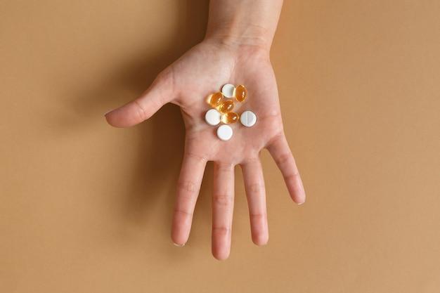Comprimidos e vitaminas na palma da mão de uma mulher
