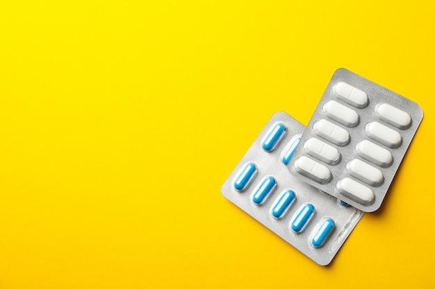 Comprimidos em blister em fundo amarelo, espaço para texto