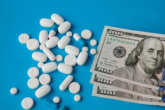 Comprimidos em dinheiro do dólar sobre fundo azul. despesas com medicamentos. altos custos do conceito de medicação. fechar-se.