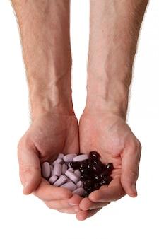 Comprimidos em duas mãos masculinas isoladas no branco