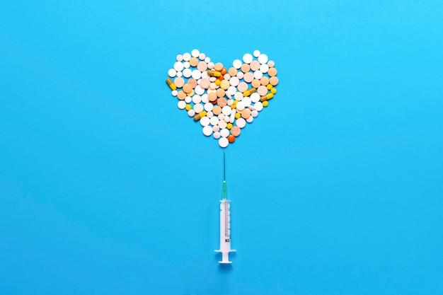 Comprimidos em forma de um coração e uma seringa presa sobre um fundo azul. conceito da indústria farmacêutica, medicina, tratamento e recuperação após doenças cardiovasculares. vista plana, vista superior