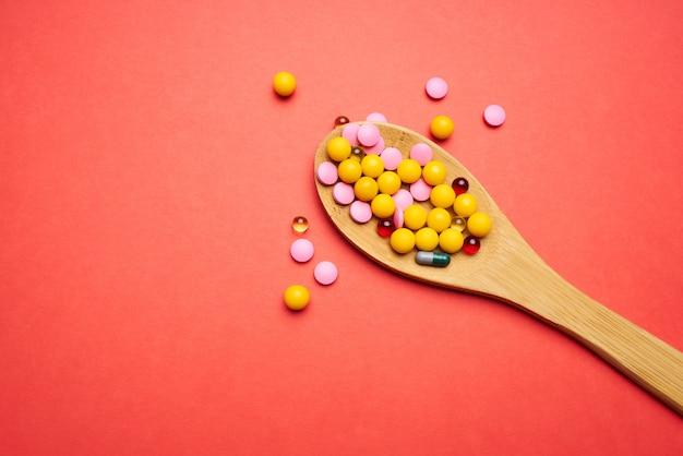 Comprimidos em uma colher sobre fundo vermelho vista superior antibióticos remédios