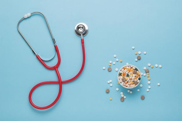 Comprimidos espalhados de uma tigela branca e um estetoscópio vermelho sobre um fundo azul. o conceito de tratamento de várias doenças. postura plana.
