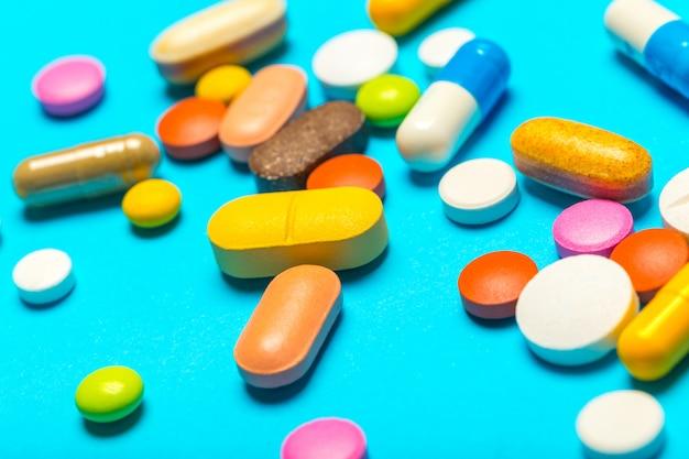 Comprimidos estão espalhados sobre um fundo azul