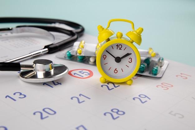 Comprimidos, estetoscópio, despertador e calendário em uma mesa, cronograma para verificar o conceito saudável.