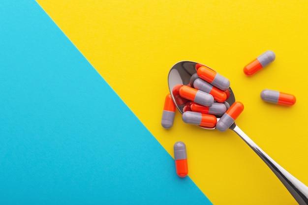 Comprimidos farmacêuticos em colher em fundo azul amarelo