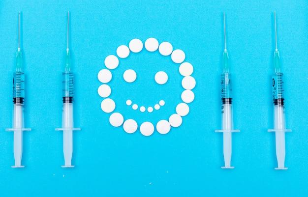 Comprimidos formando feliz emoji com agulhas ao redor