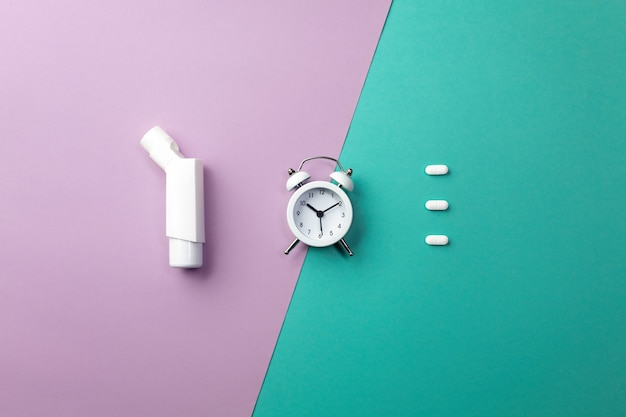 Comprimidos, inalador e despertador branco sobre fundo colorido. conceito de medicina e saúde em estilo minimalista