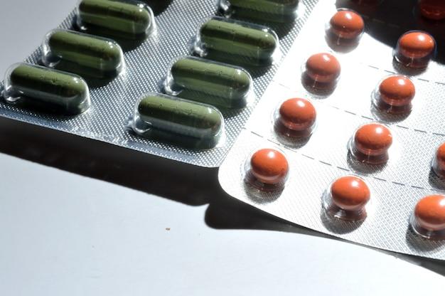 Comprimidos laranja e verdes em uma bolha de papel alumínio mentem sobre um fundo claro. grande iplan. vista de cima