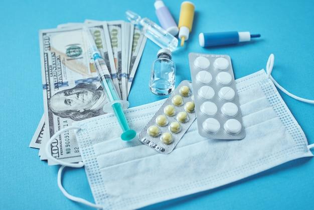 Comprimidos, máscara protetora, itens médicos e notas de dólar em fundo escuro