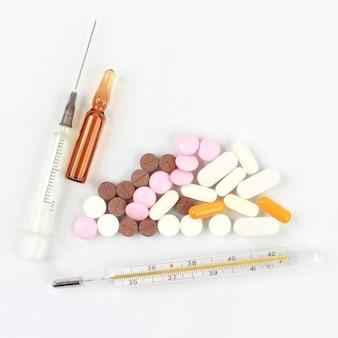 Comprimidos medicinais, ampolas para injeções, termômetro, seringa em fundo branco