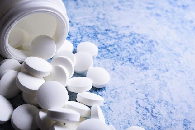 Comprimidos médicos brancos e comprimidos derramando de um frasco de medicamento. vista macro de cima para baixo com espaço de cópia.