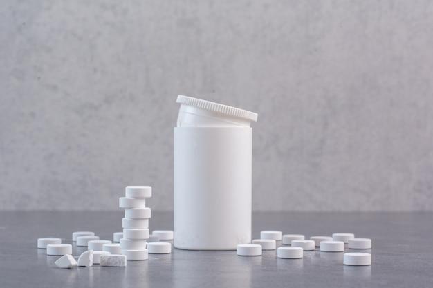 Comprimidos médicos brancos e recipiente de plástico vazio.