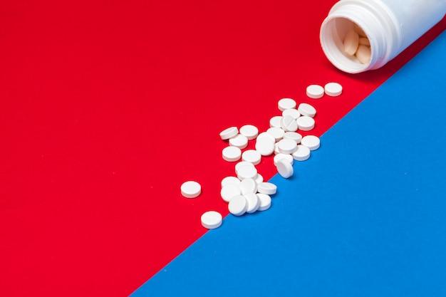 Comprimidos médicos brancos em um vermelho e azul de duas cores