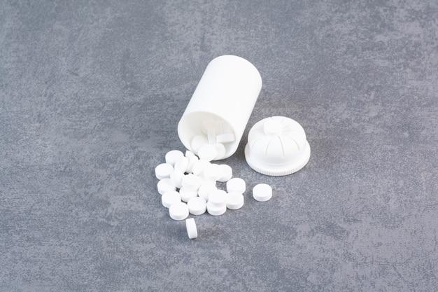 Comprimidos médicos brancos fora do recipiente de plástico.