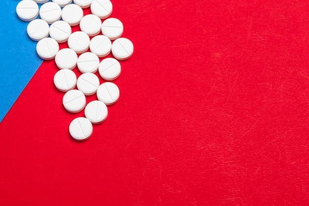 Comprimidos médicos brancos sobre um fundo vermelho e azul de duas cores
