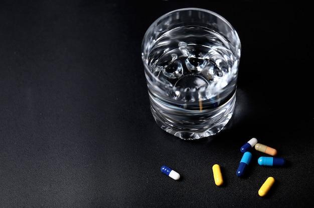 Comprimidos médicos com um copo de água. vista do topo.