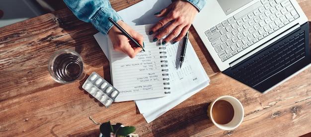 Comprimidos médicos e copo de água pela mulher escrevendo notas