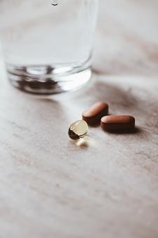Comprimidos médicos e copo de água, saúde e bem-estar, closeup