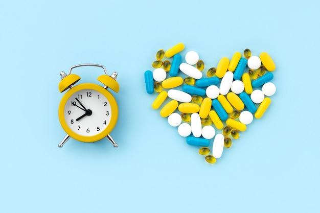 Comprimidos médicos em formato de coração com despertador em azul