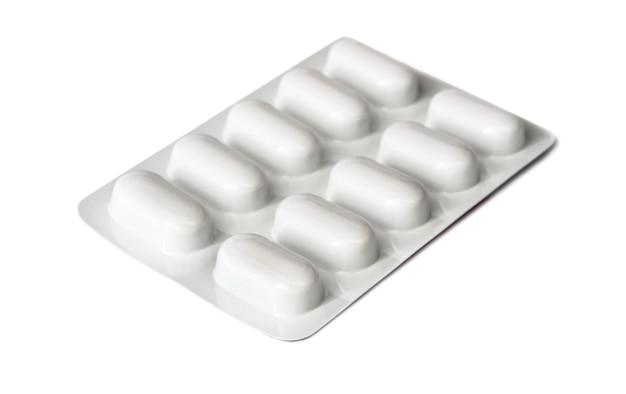 Comprimidos médicos em placa de plástico isolados no fundo branco