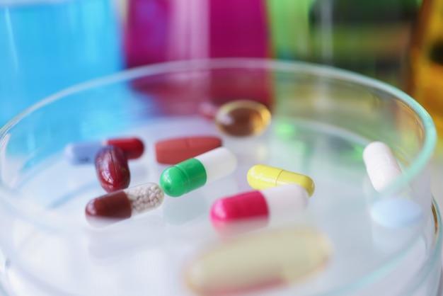 Comprimidos médicos multicoloridos repousam no conceito de indústria farmacêutica de tubo de ensaio de vidro