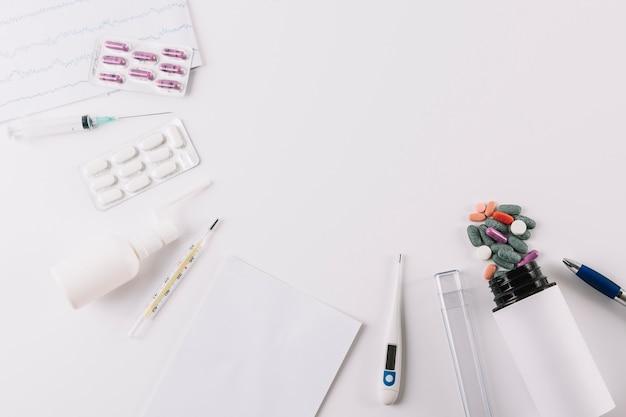 Comprimidos médicos; seringa e termômetro isolado no fundo branco