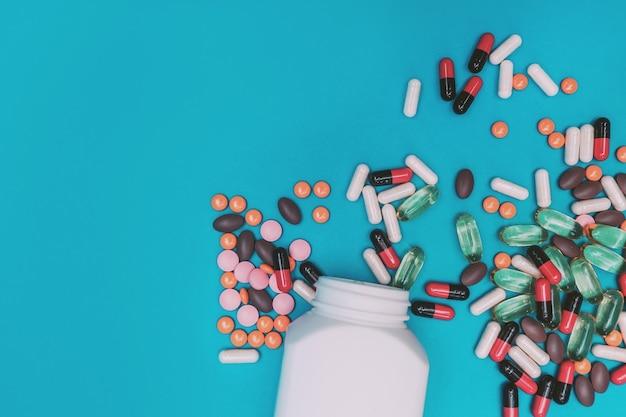 Comprimidos multicoloridos caindo de um frasco em um fundo azul