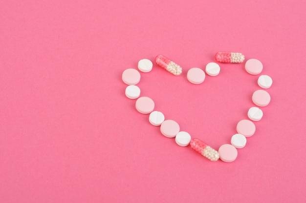 Comprimidos multicoloridos, cápsulas são dispostas na forma de um coração em um fundo rosa. doenças cardíacas. conceito de cuidados de saúde.