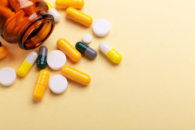 Comprimidos multicoloridos e cápsulas de comprimidos de garrafa de vidro amarelo