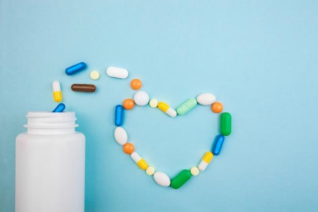 Comprimidos multicoloridos e cápsulas em forma de coração com frasco branco para comprimidos