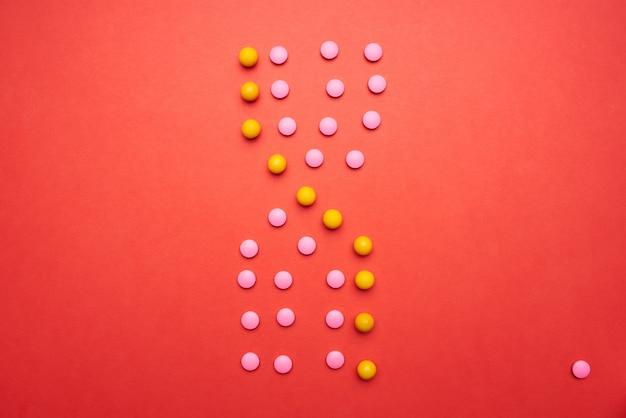 Comprimidos multicoloridos em fundo vermelho, vista superior, produtos farmacêuticos para a saúde