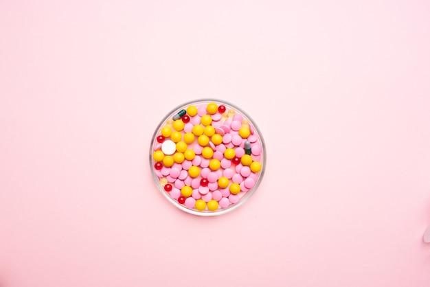 Comprimidos multicoloridos, remédios para analgésicos, fundo rosa