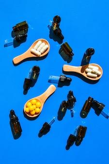 Comprimidos na colher de pau e conta-gotas sobre fundo azul. luz e sombras fortes. conceito de minimalismo criativo. vitaminas e prebióticos, probióticos. dose de vitamina no outono.