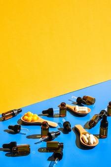 Comprimidos na colher de pau e pipeta conta-gotas em fundo azul e amarelo. luz e sombras fortes. conceito moderno de minimalismo criativo isométrico. vitaminas e prebióticos, probióticos. dose de vitamina no outono.