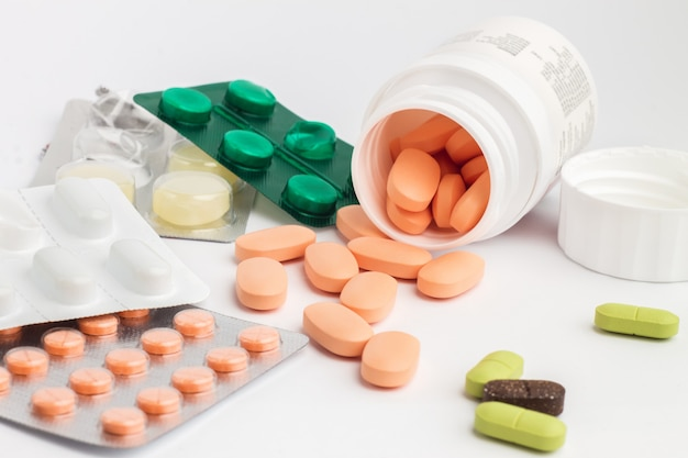 Comprimidos na embalagem e comprimidos derramando fora uma garrafa em branco