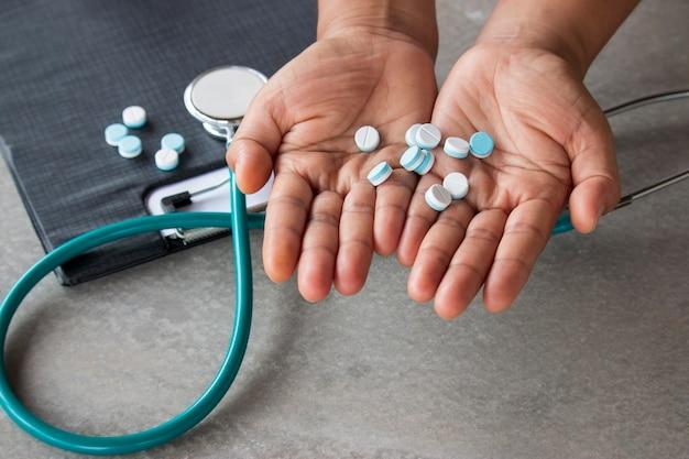 Comprimidos na mão e instrumentos médicos