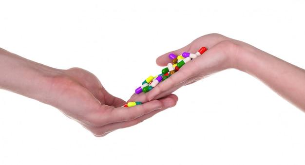 Comprimidos na mão, isolado no fundo branco