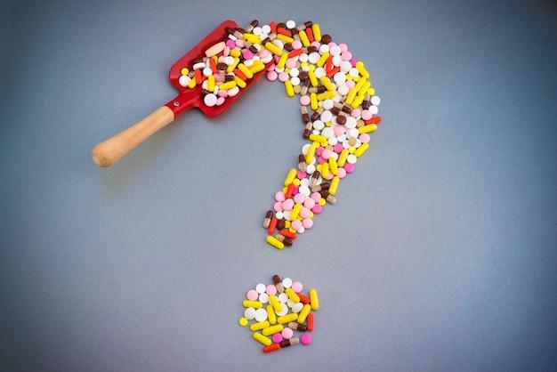 Comprimidos ou cápsulas como um ponto de interrogação.