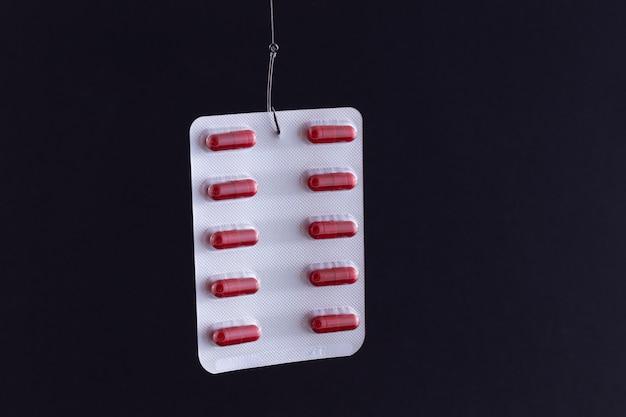 Comprimidos ou comprimidos vermelhos em um pacote pendurado em um anzol de pesca
