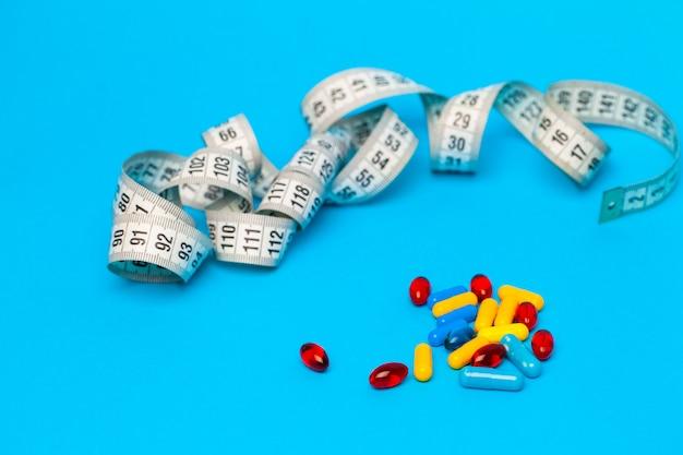Comprimidos para perda de peso e fita métrica em azul.