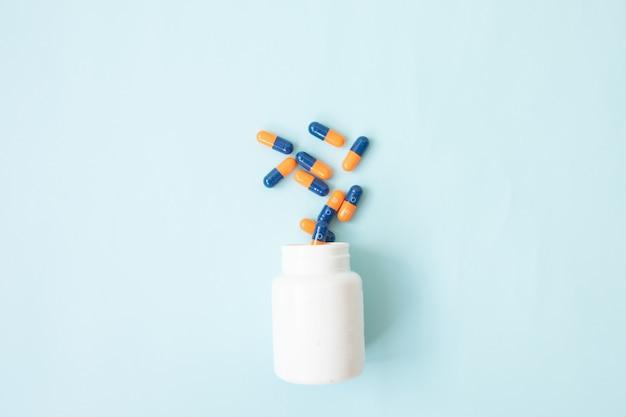 Comprimidos que derramam fora do frasco de comprimido e isolados no azul. vista superior com espaço de cópia.