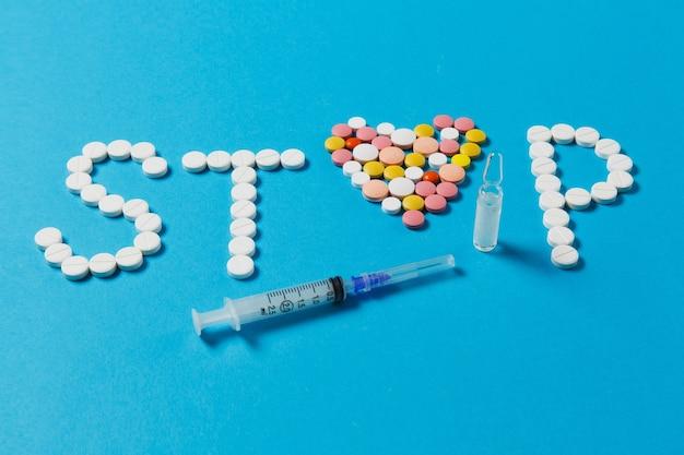 Comprimidos redondos brancos, coloridos de medicação em palavra parar isolado sobre fundo azul. pílulas de coração, ampola, agulha da seringa vazia. conceito de escolha de tratamento, estilo de vida saudável. copie o anúncio do espaço.